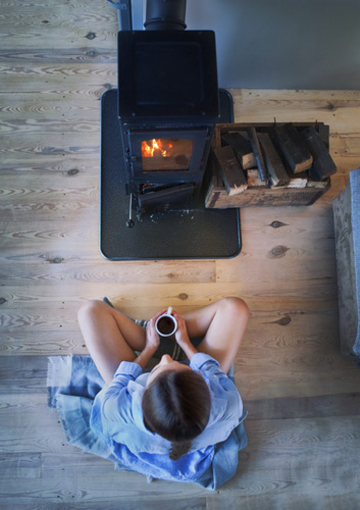 Young brunette woman sitting down on the floor by the fireplace